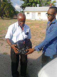 Manager of The Maxfield Park Children's Home in Kingston Jamaica Winston Bowen (l) receiving goods from Veli for the home's wards